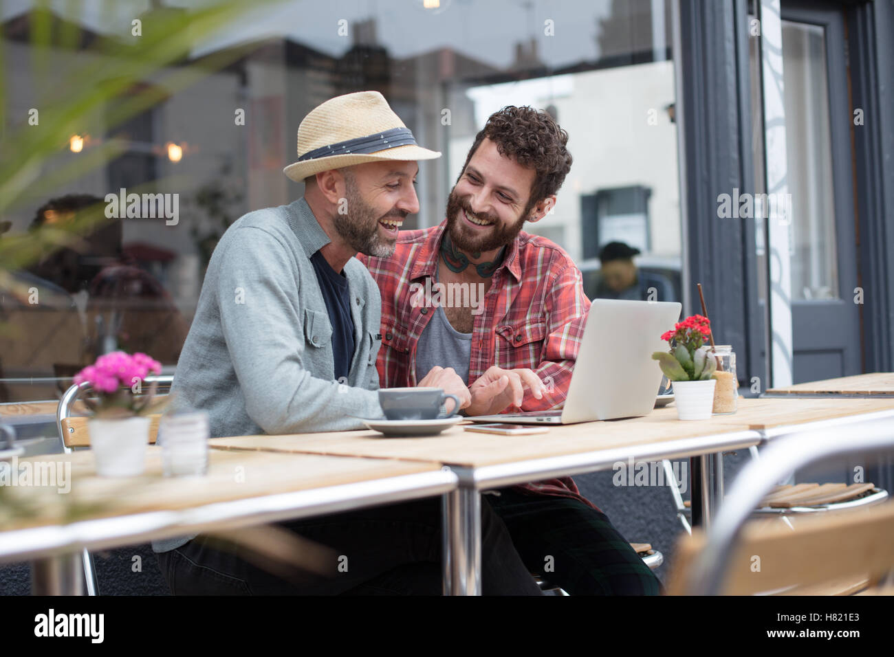 Gay couple sat sharing laptop in cafe - Stock Image