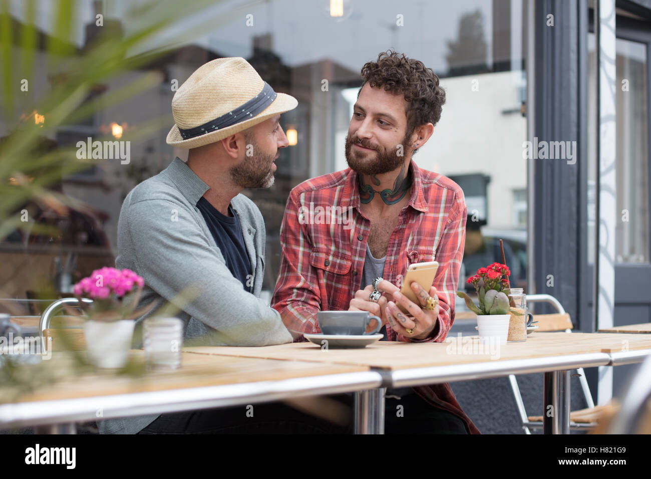 Gay couple sharing phone in cafe - Stock Image