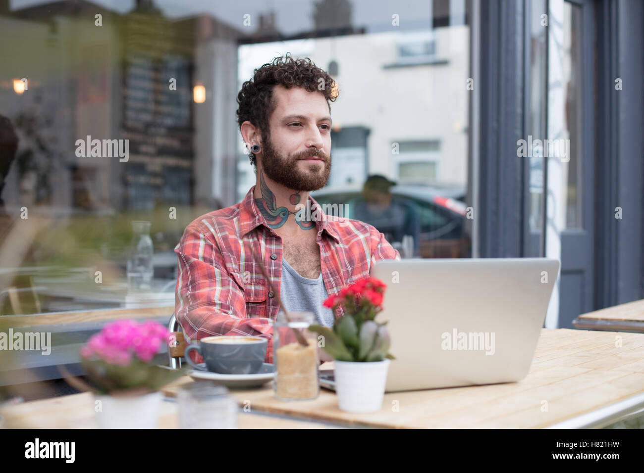 Young tattooed hipster using laptop outside cafe - Stock Image