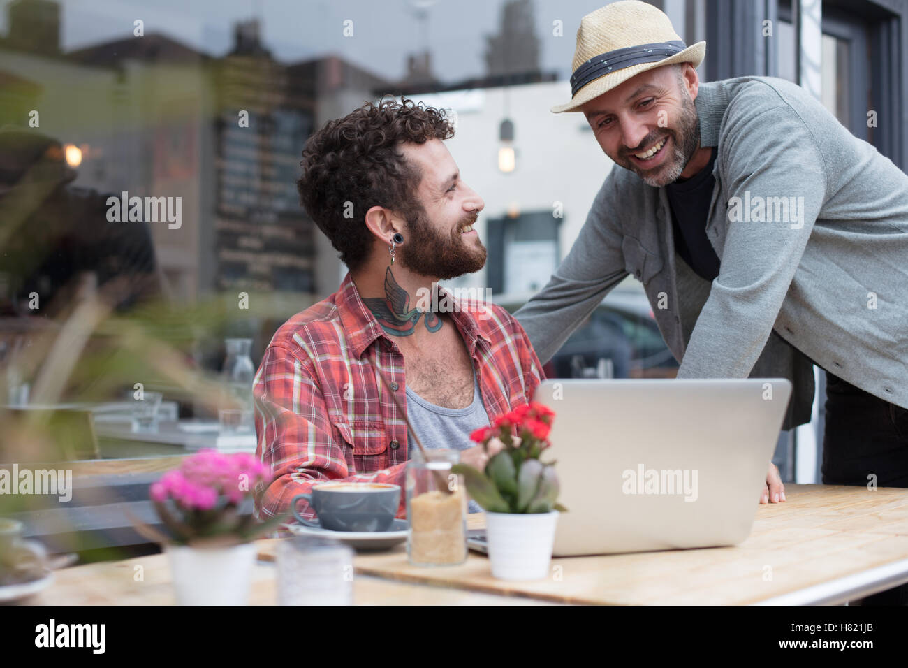 Gay couple sharing laptop in cafe - Stock Image