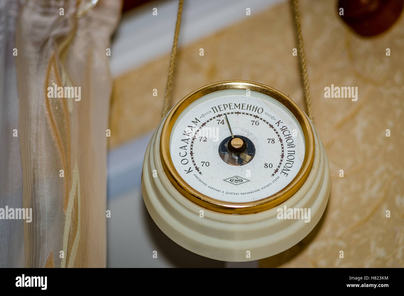 The barometer hanging on the wall in the apartment of the unit of measurement of atmospheric pressure - Stock Image
