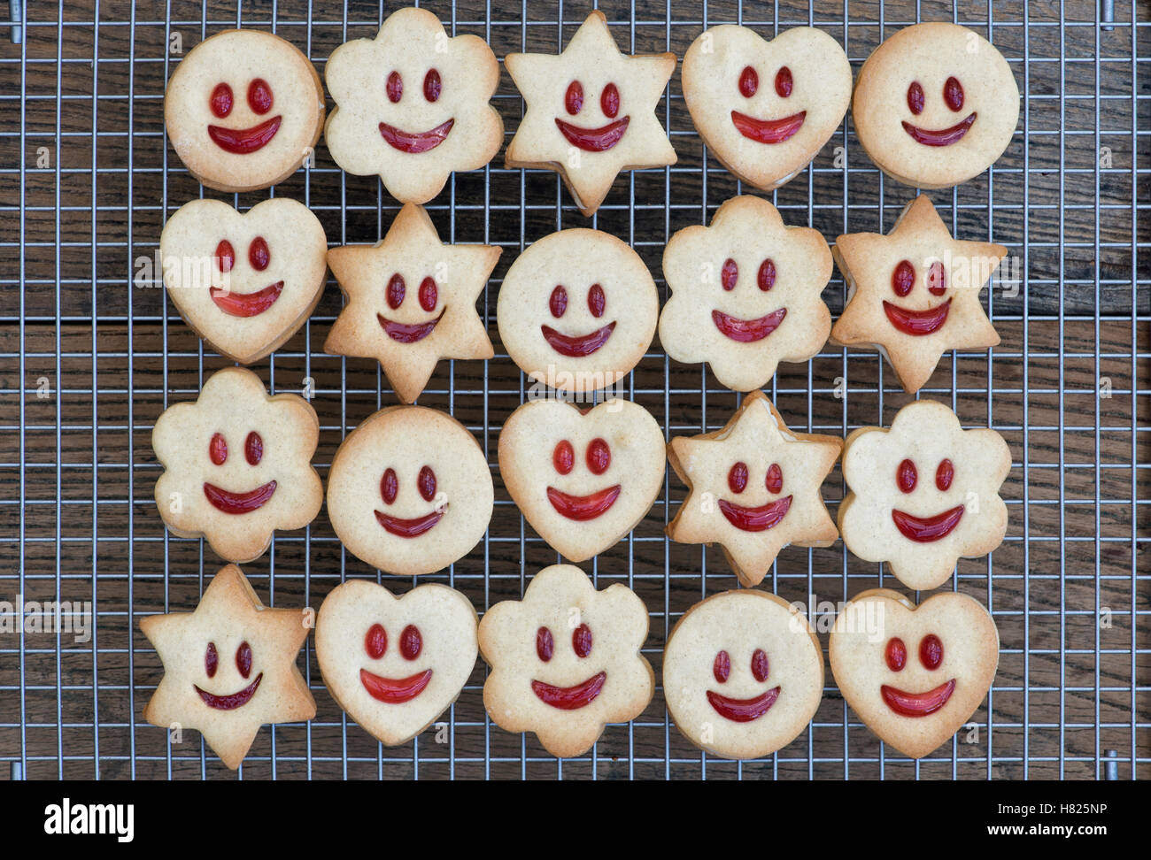 Homemade Jammie Dodgers. Smiling face biscuits faces on a wire rack - Stock Image