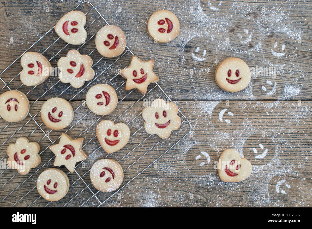 Homemade Jammie Dodgers. Smiling face biscuits and icing sugar impressions on wood - Stock Image