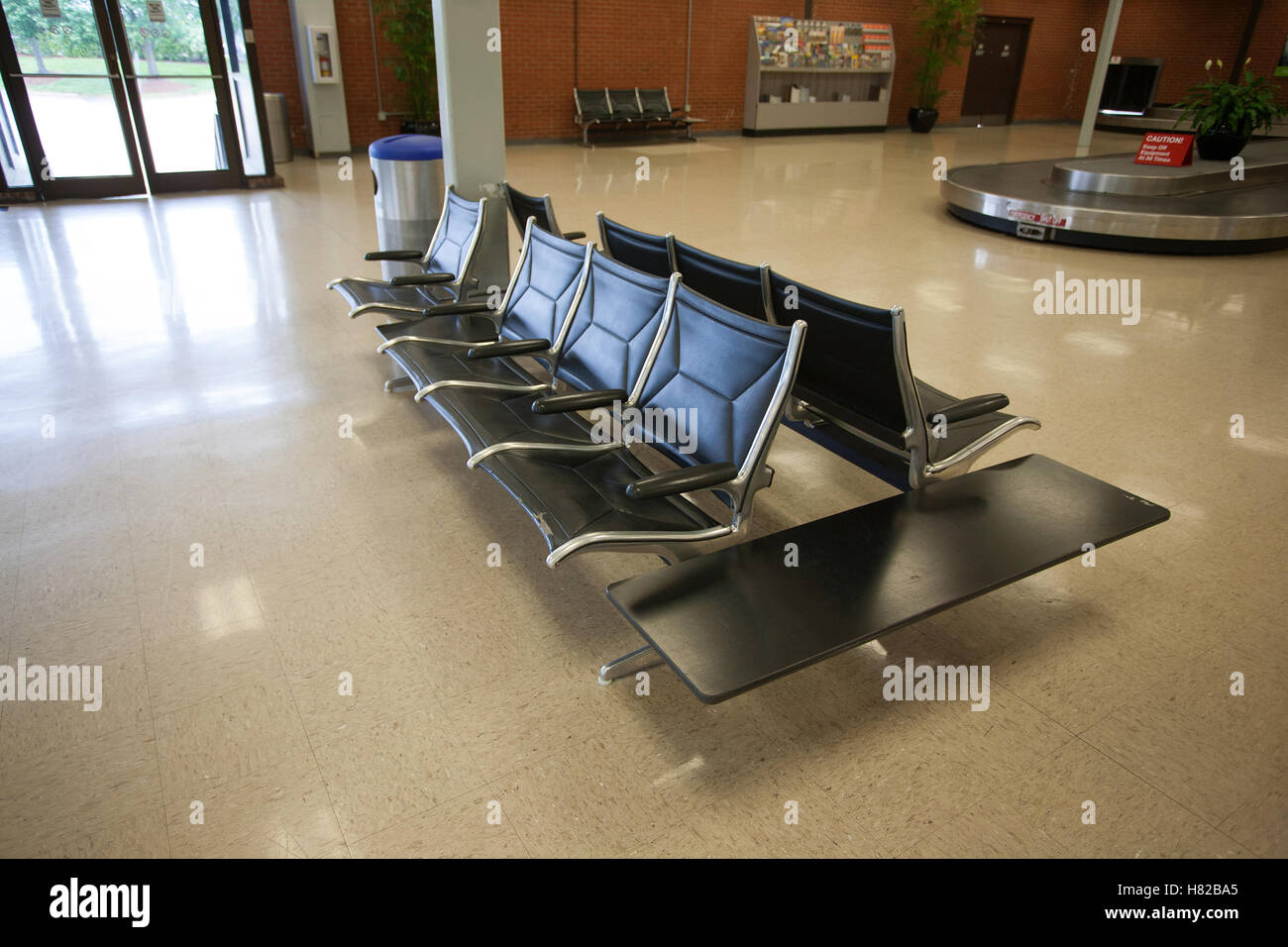 Plenty of room to sit in an airport luggage claim area - Stock Image