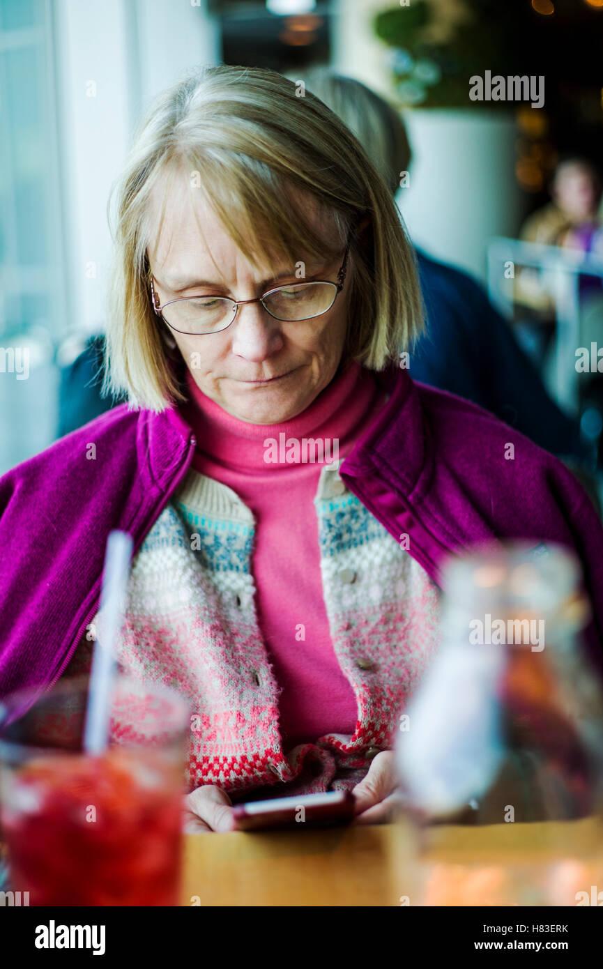 Woman seated at indoor restaurant cafe checking her smart phone; Denver International Airport; Denver; Colorado; - Stock Image