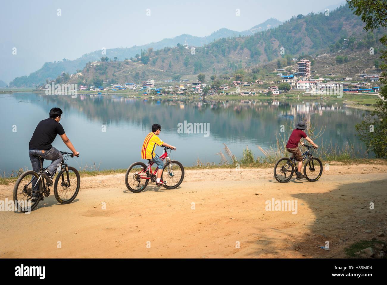 Family ride bicycles along Phewa lakeside near Pokhara, Kaski district, Nepal. © Reynold Sumayku - Stock Image