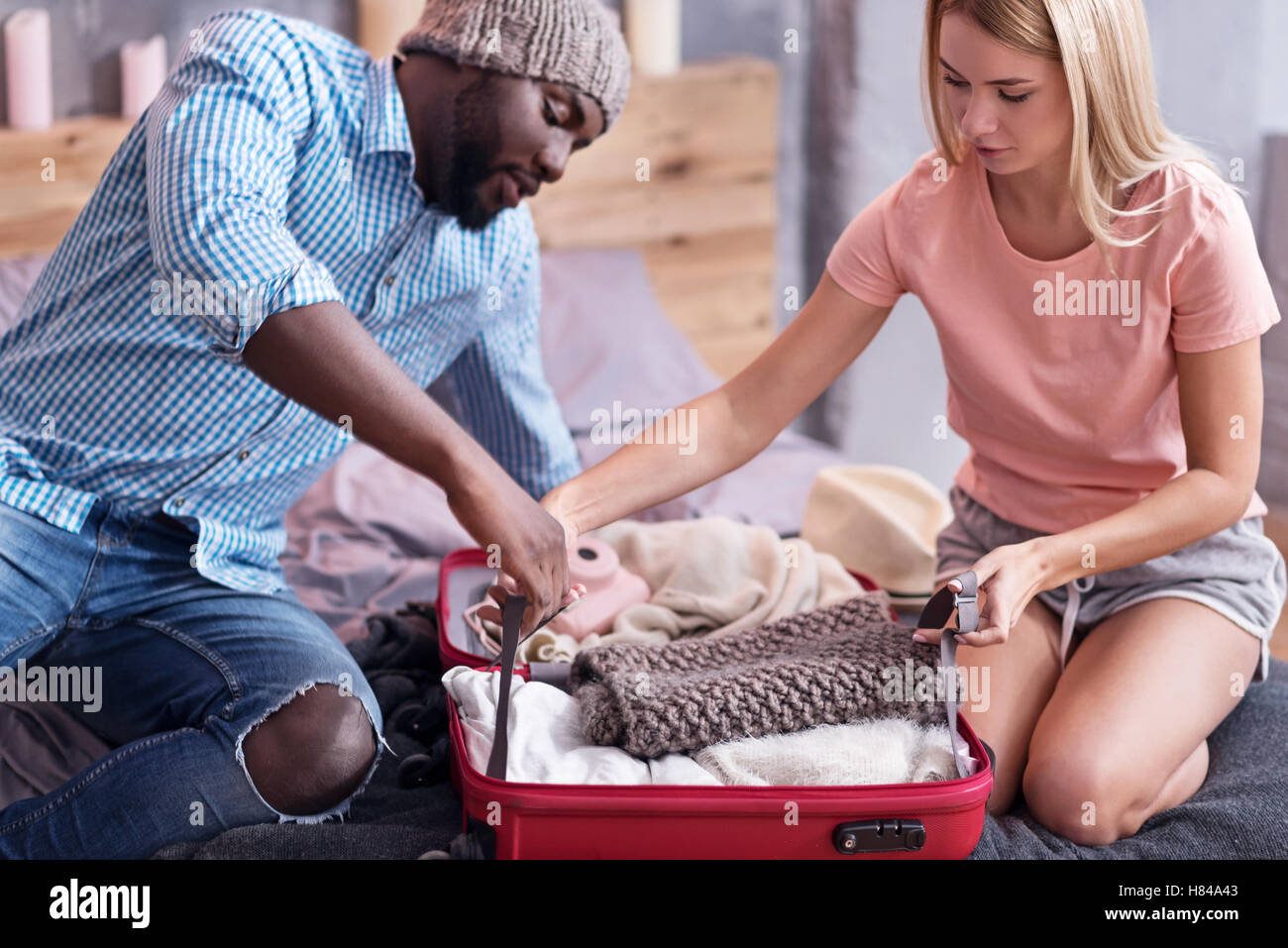 Delighted couple packing their suitcase for a journey - Stock Image