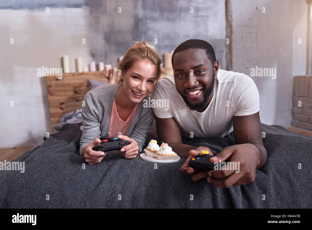 International couple playing games on console together - Stock Image