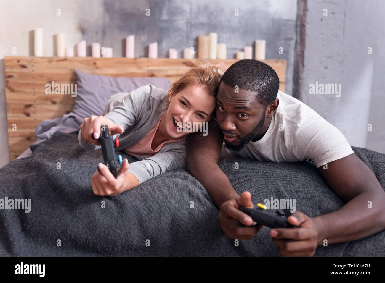 Joyful couple playing video games in bed - Stock Image