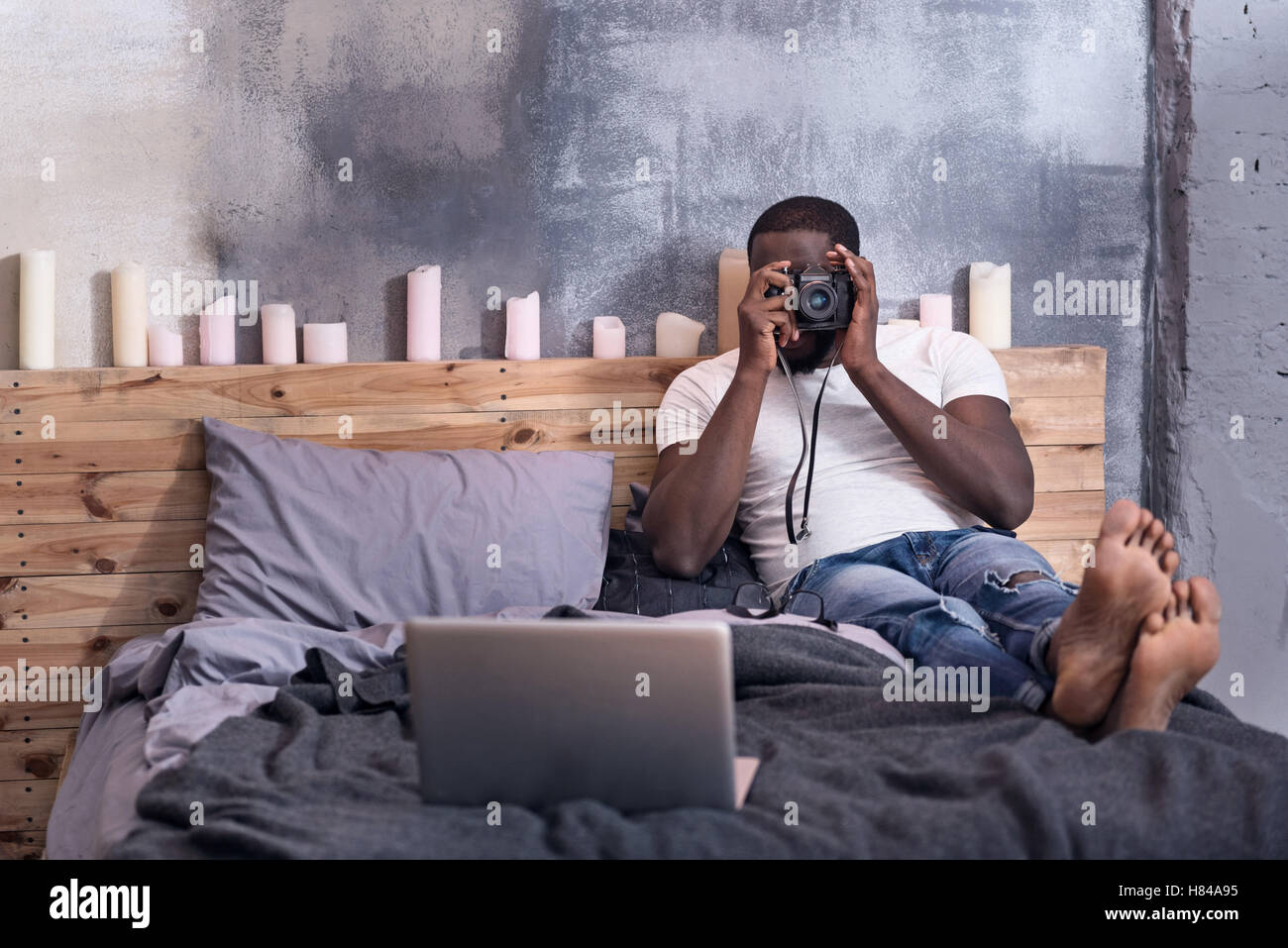 African man holding a camera in bedroom - Stock Image