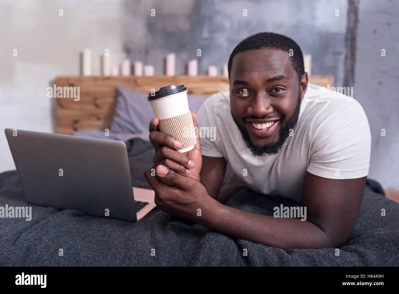 Joyful man holding cup of coffee in bedroom - Stock Image