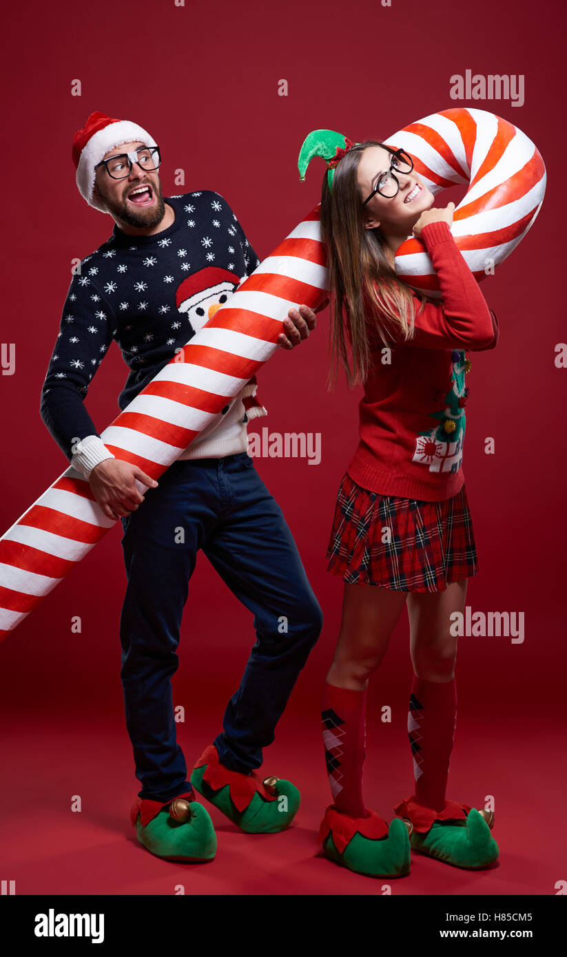 Couple carrying heavy candy cane - Stock Image