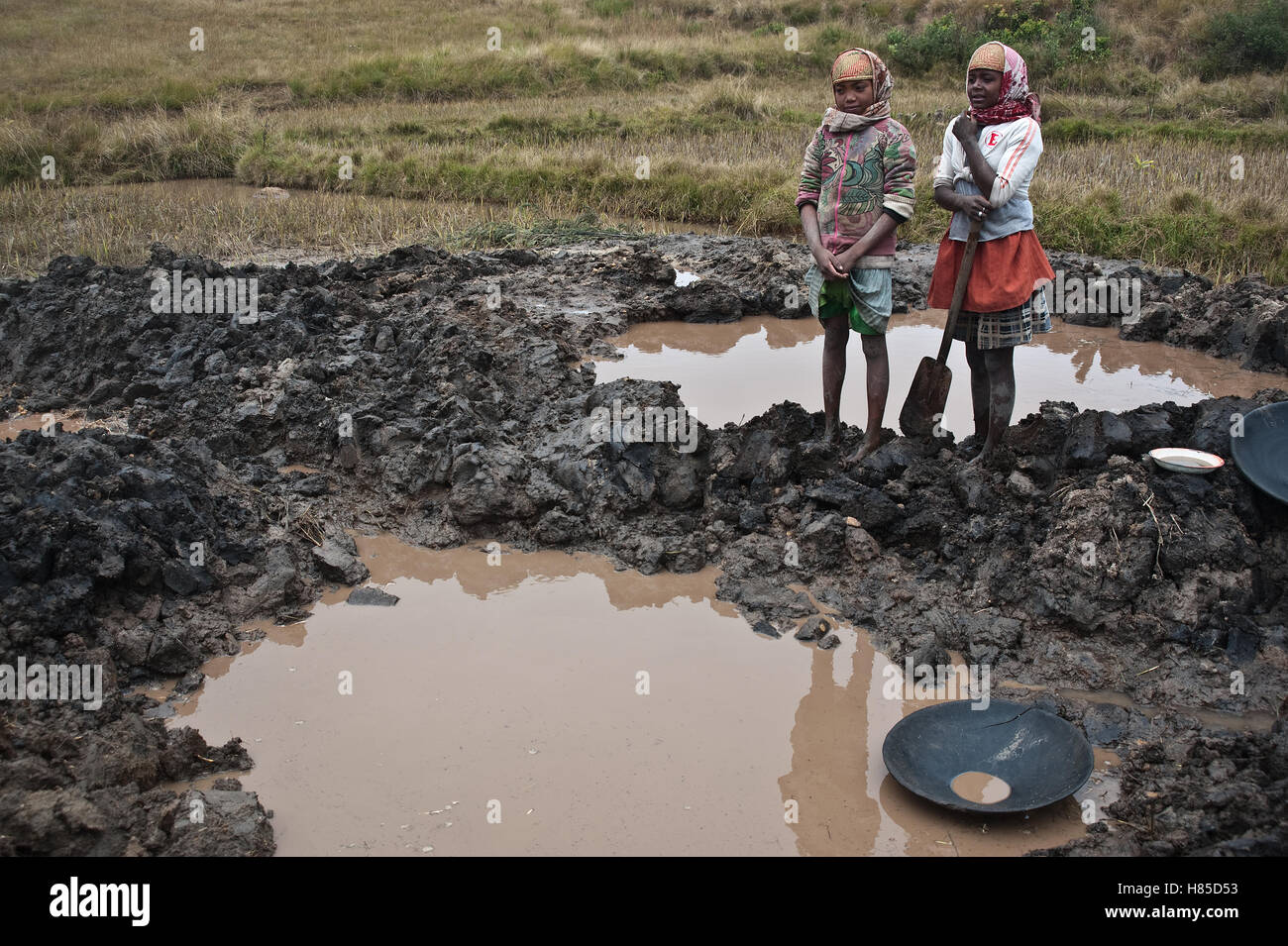 Two girls working as gold diggers. In the foreground, a abandoned pit full of water ( Madagascar) - Stock Image