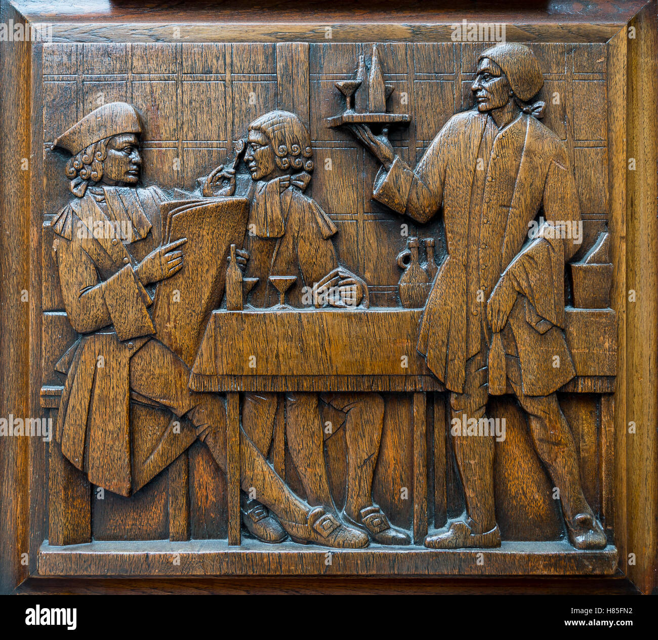 Vintage scene carved in wood relief of a well-dressed British aristocrat sitting at a dining table being waited - Stock Image