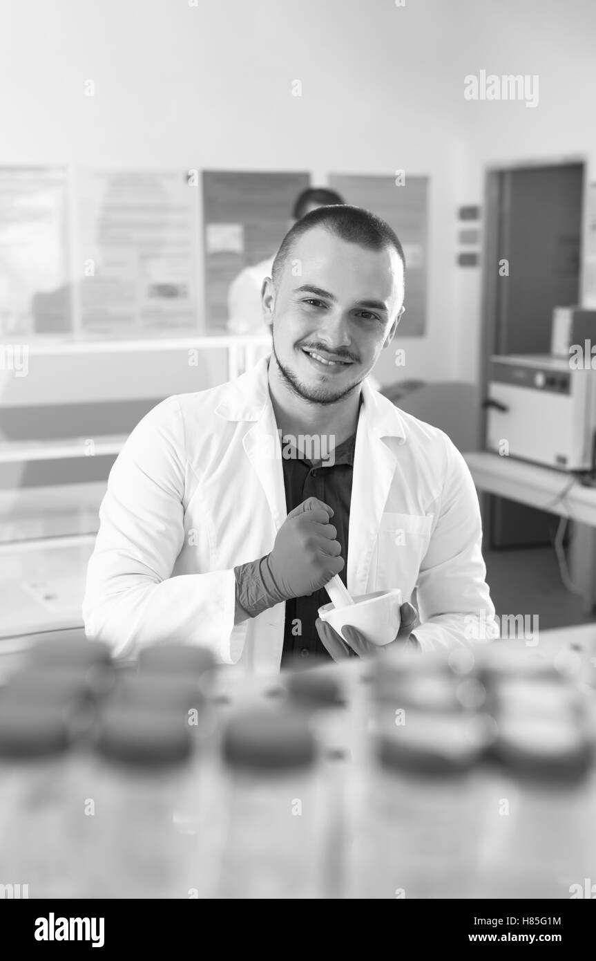 Young scientist in while lab coat smiles at the camera - Stock Image