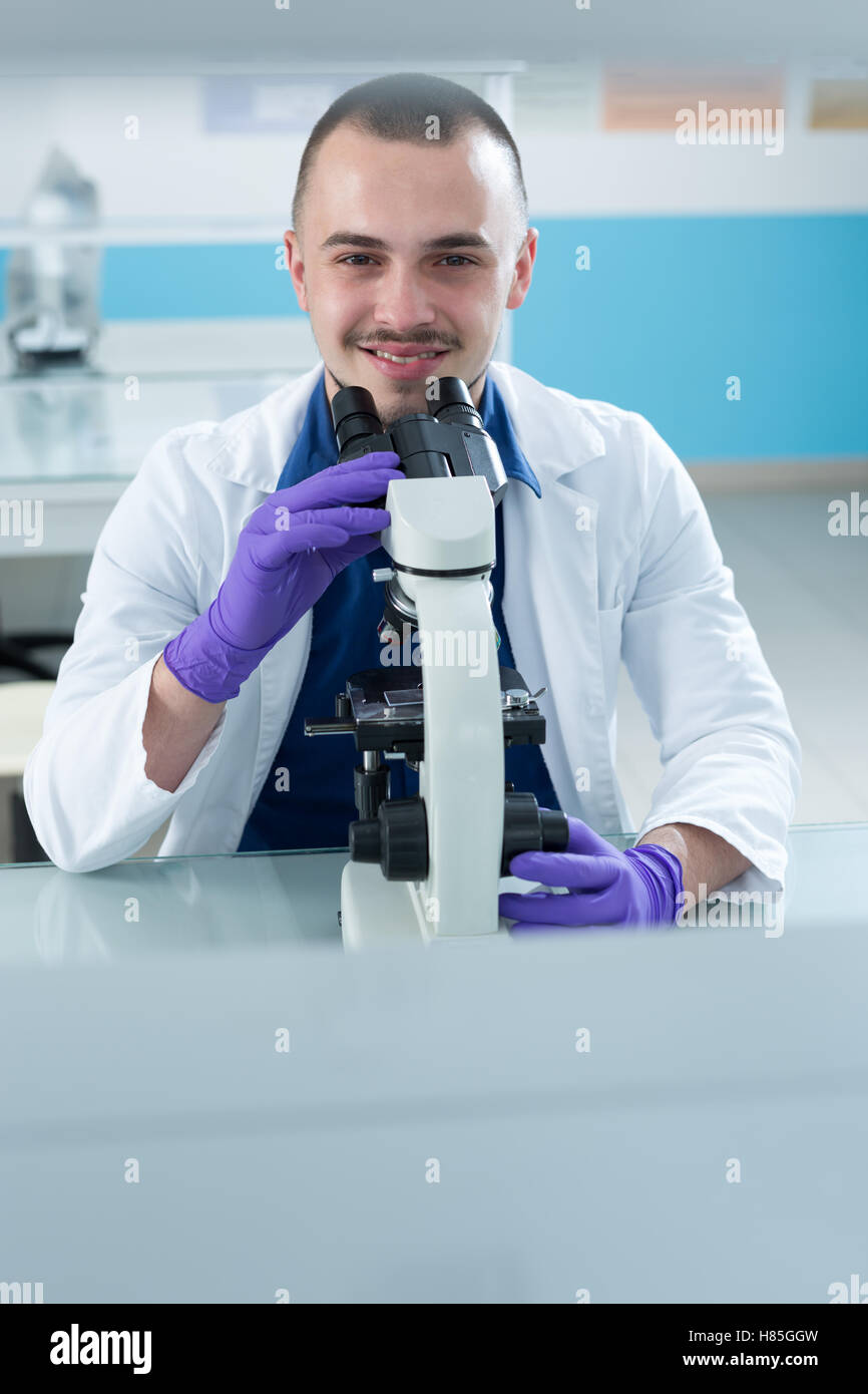 Young scientist investigating microbiological substance in microscope - Stock Image