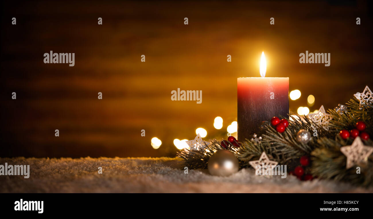 Burning candle and Christmas decoration over snow and wooden background, elegant low-key shot with festive mood - Stock Image