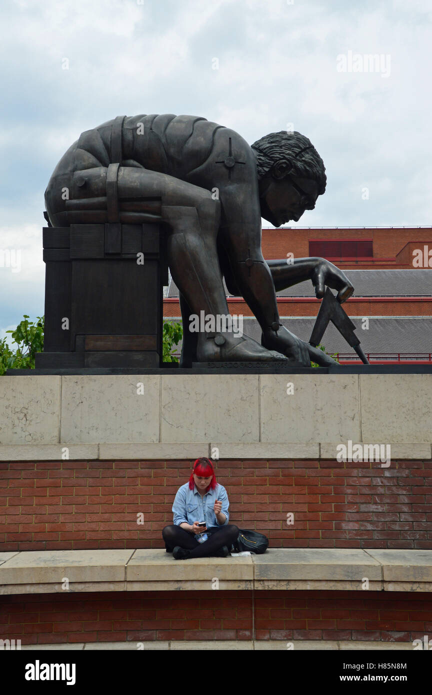 Girl sitting below statue of Isaac Newton, British Library, London - Stock Image