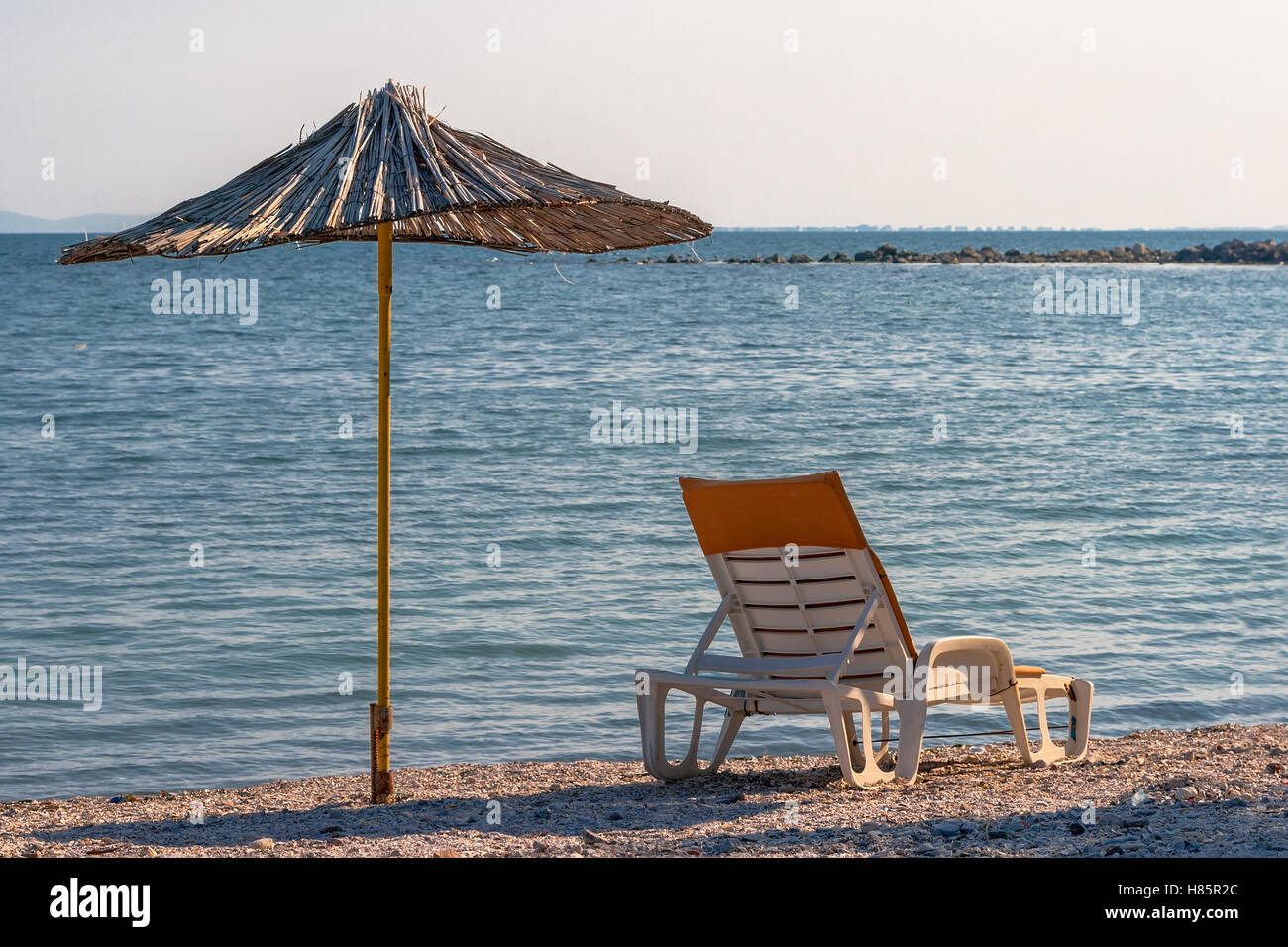 Sunbed and parasol made ​​of bamboo on the beach - Stock Image