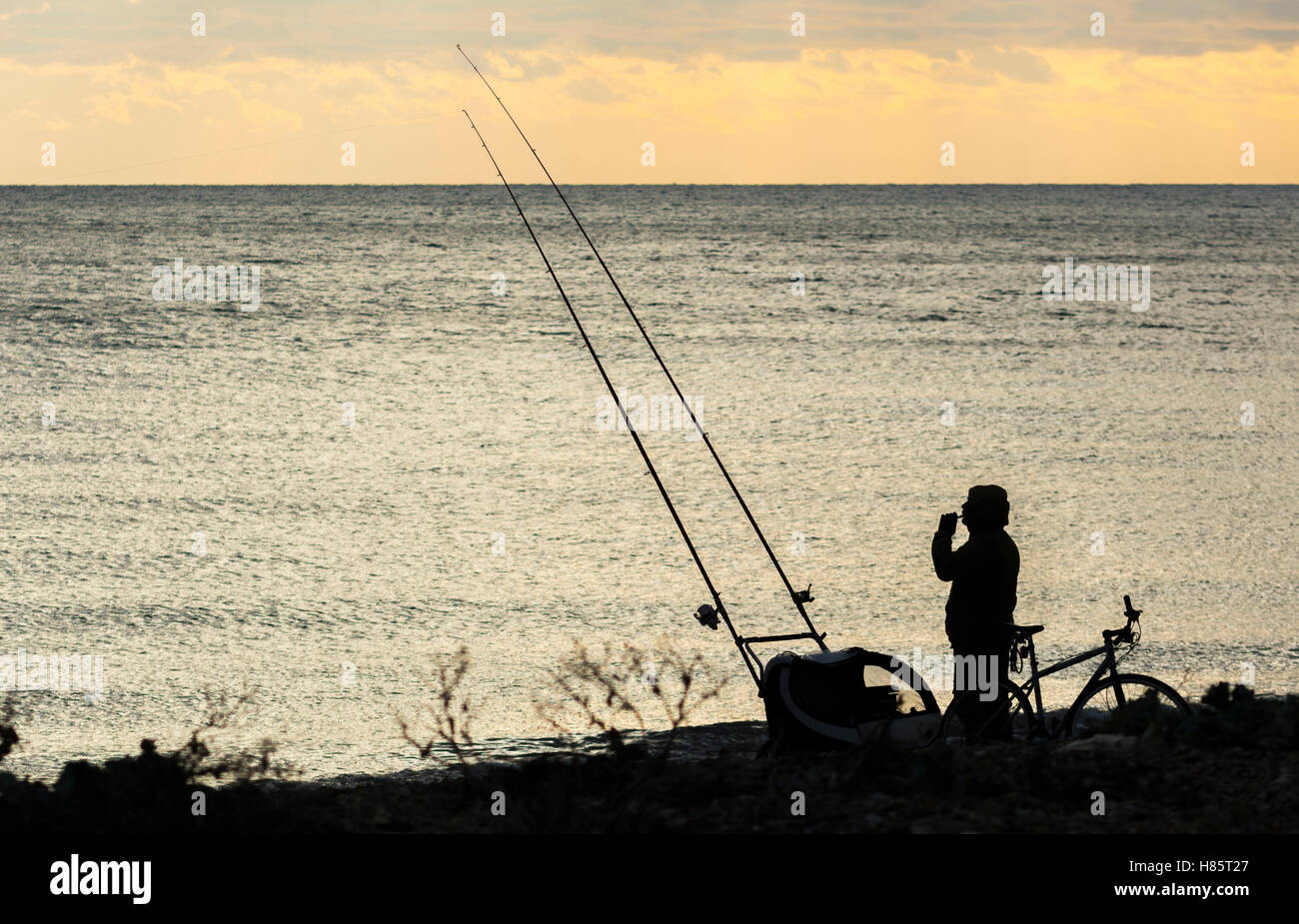 Silhouette of someone fishing at sea. - Stock Image