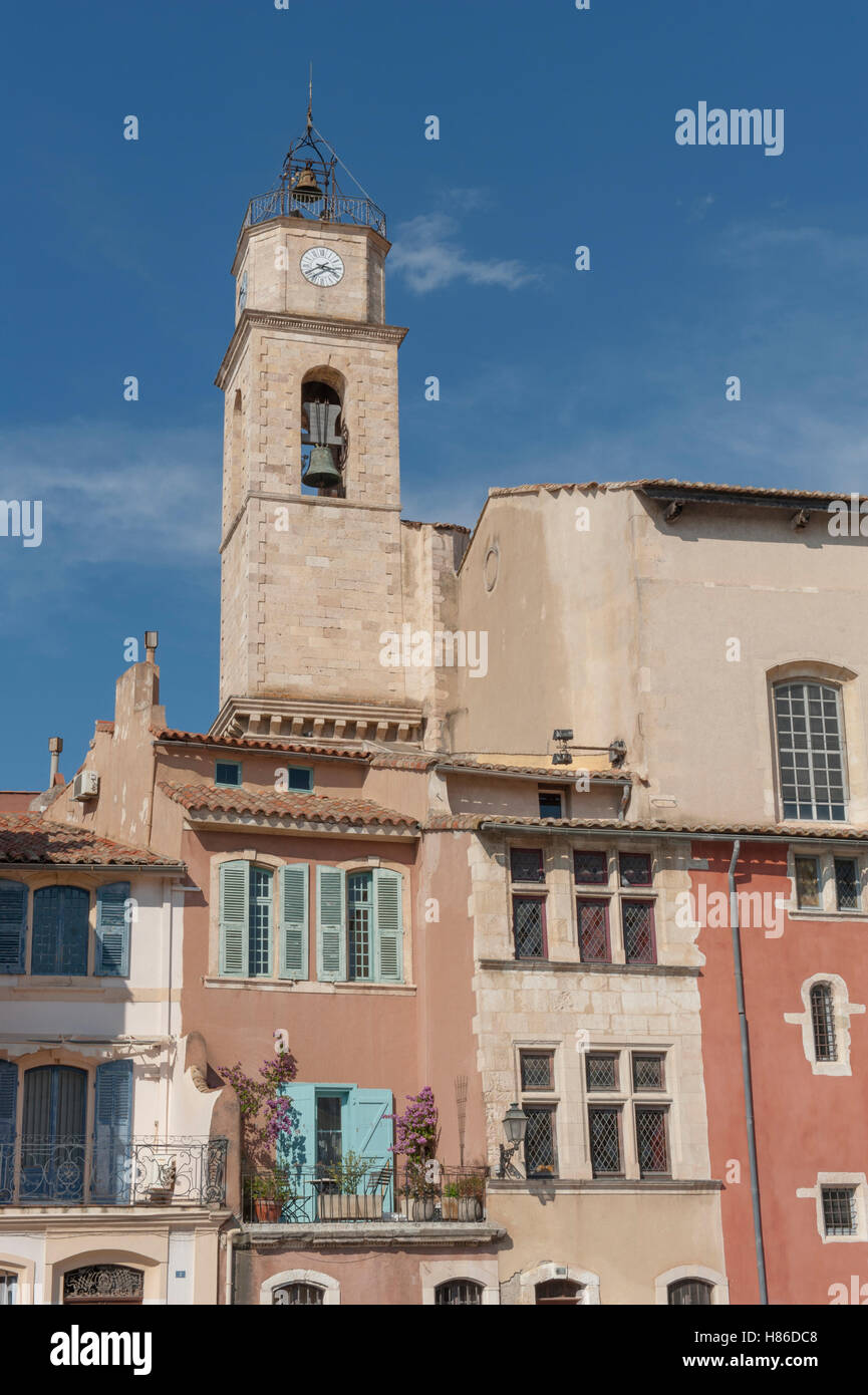 The tower of the church Église Sainte Marie-Madeleine hovers above the old homes at Quay Marceau, Provence, - Stock Image