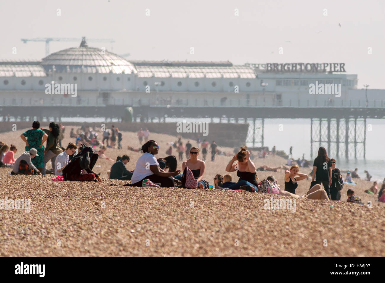 People enjoying the spring weather on Brighton beach - Stock Image