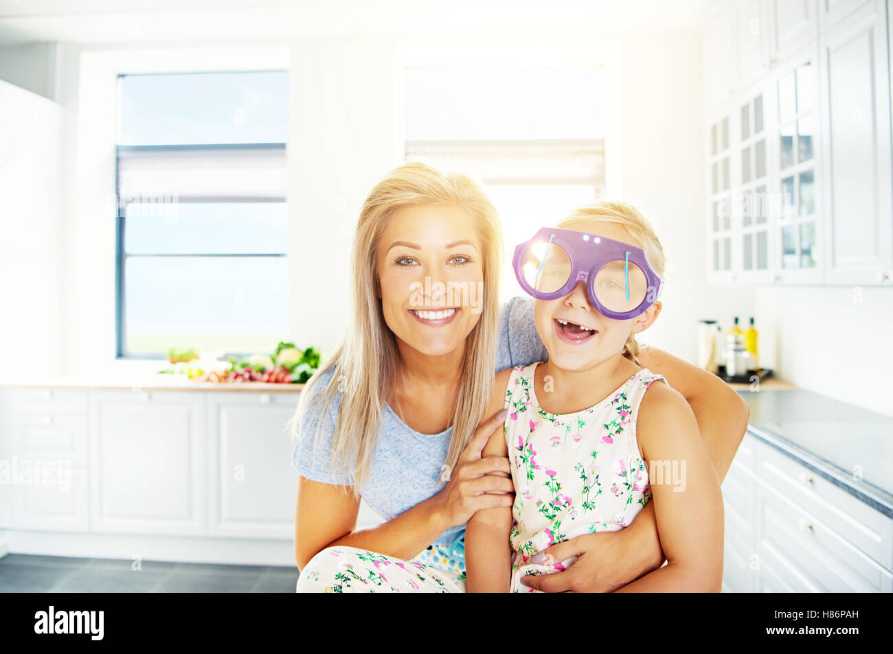 Vivacious little girl in outsized plastic glasses laughing merrily for the camera as she is hugged by her loving - Stock Image