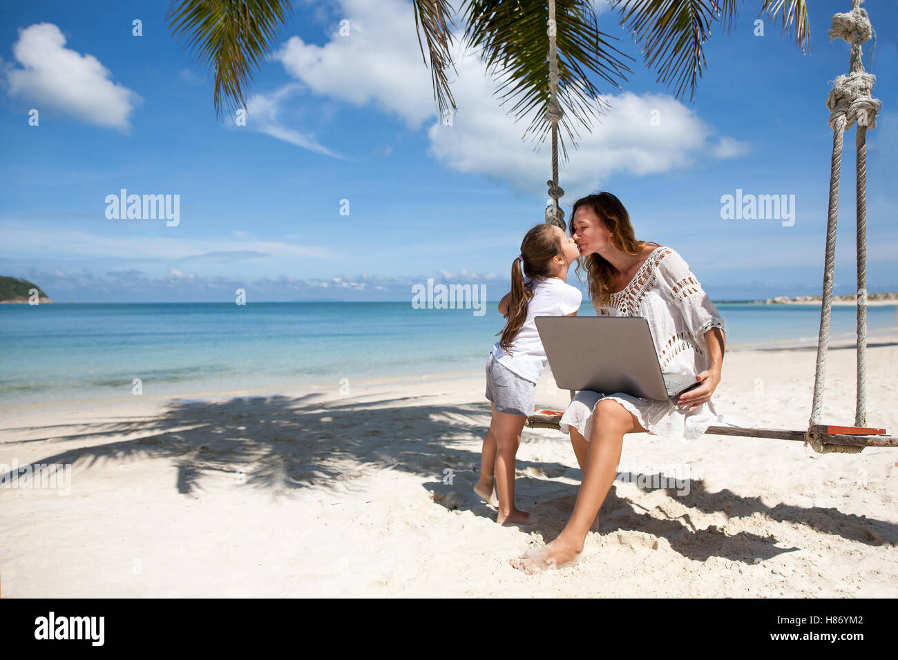 Women freelance on a beach with laptop - Stock Image