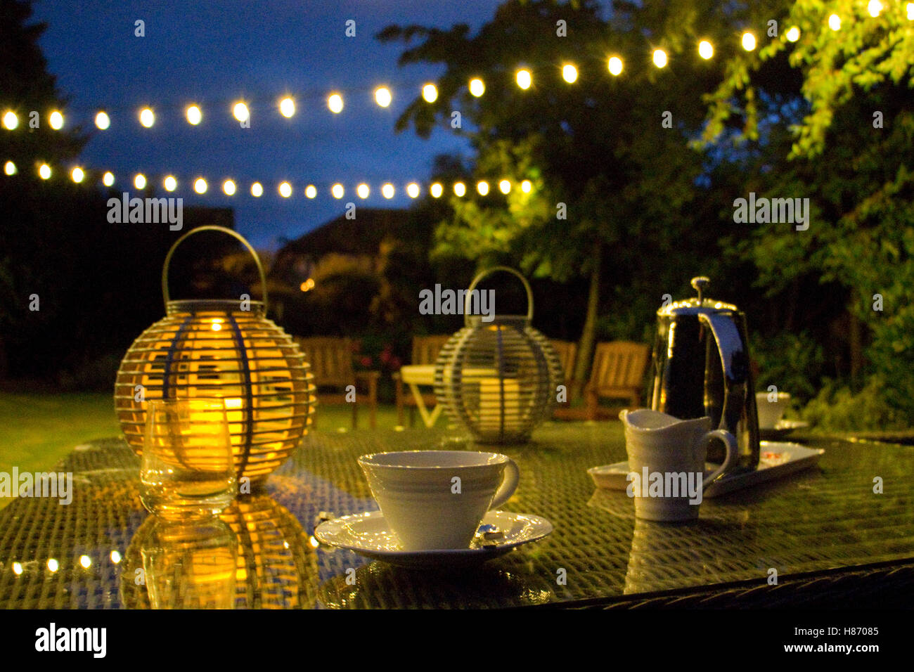 Late summer evening in an English garden with decorative lights - Stock Image