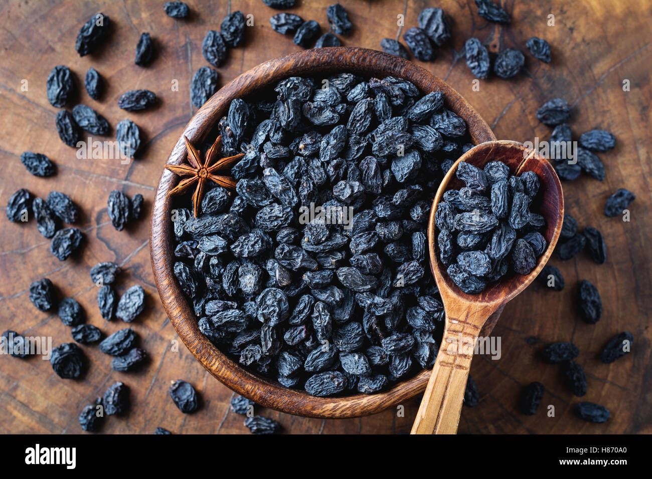 Black raisins in wooden bowl, top view. Healthy snack, dietary product for good life - Stock Image