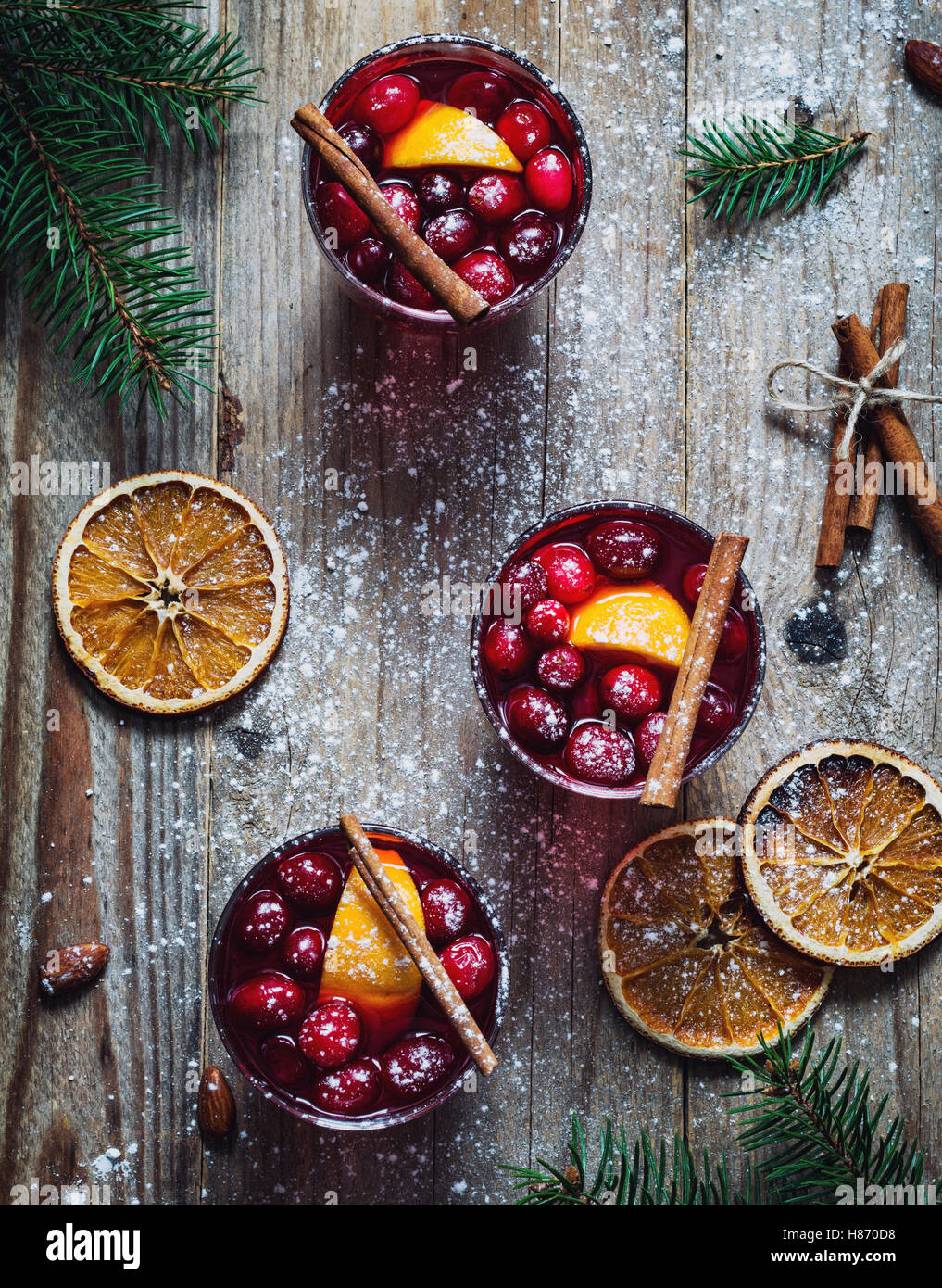 Hot spicy mulled wine with cranberries, cinnamon and orange in glasses on wooden table. Top view - Stock Image
