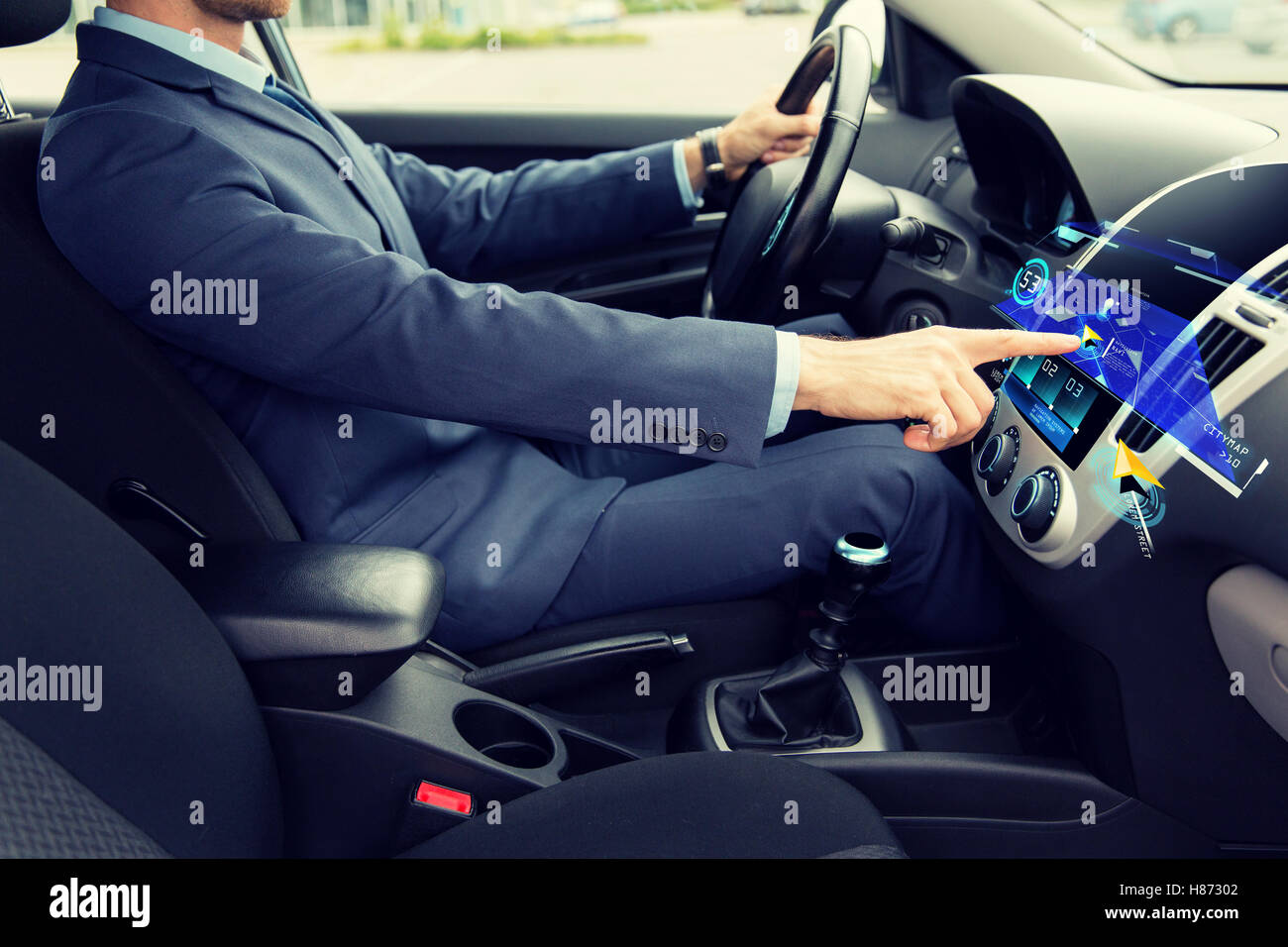 close up of man driving car with navigation - Stock Image