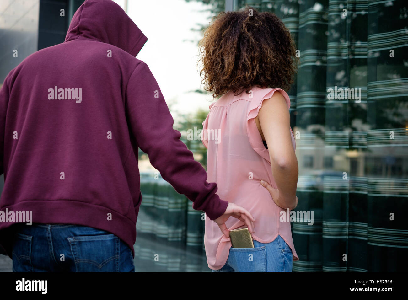 Thief stealing the mobile phone from the jeans pocket of a distracted woman - Stock Image