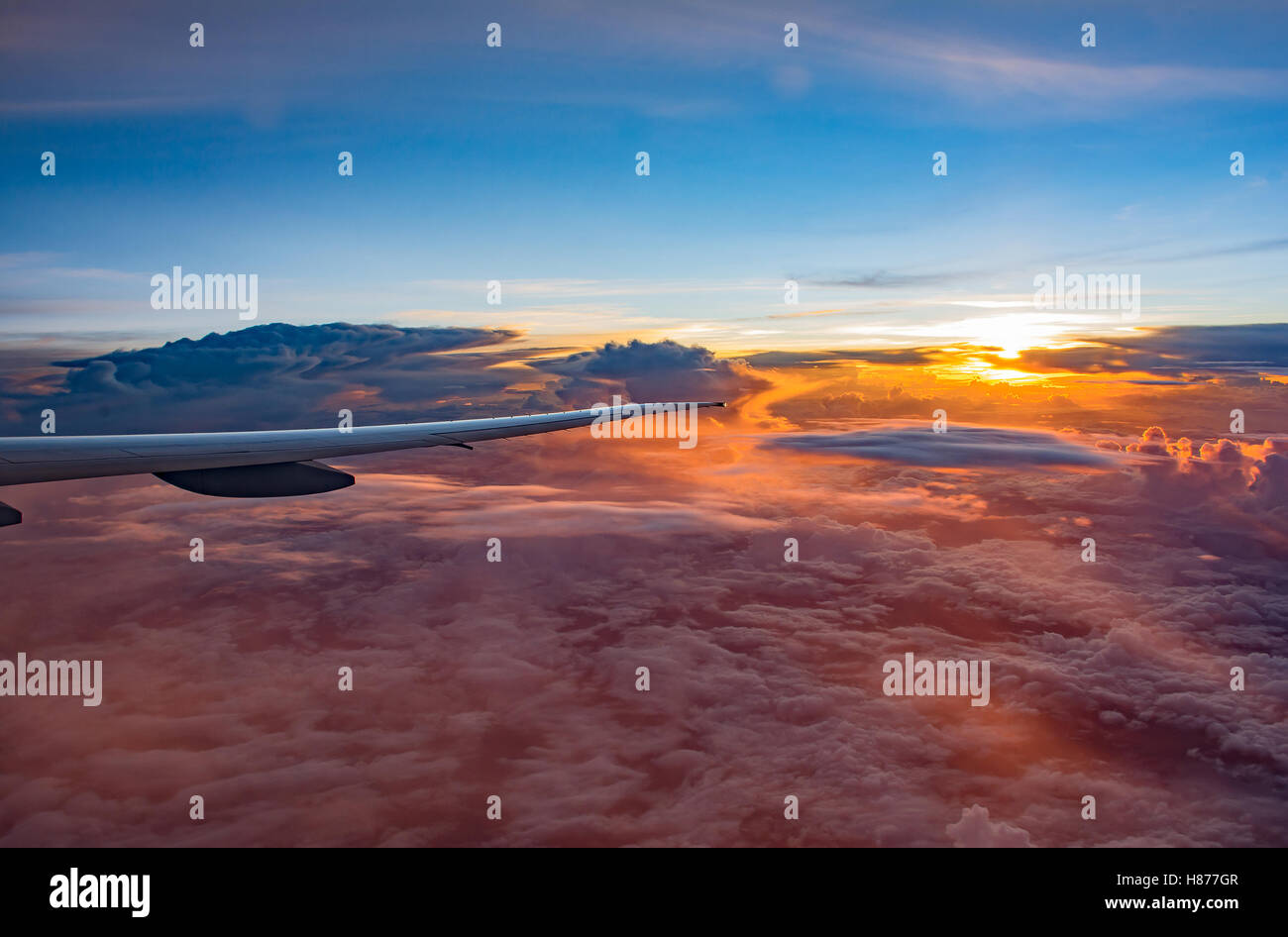 Looking From Window To Air Plane Wing In Flight With Beautiful Scenery Of Amazing Cloud Formations On Sunset Sky