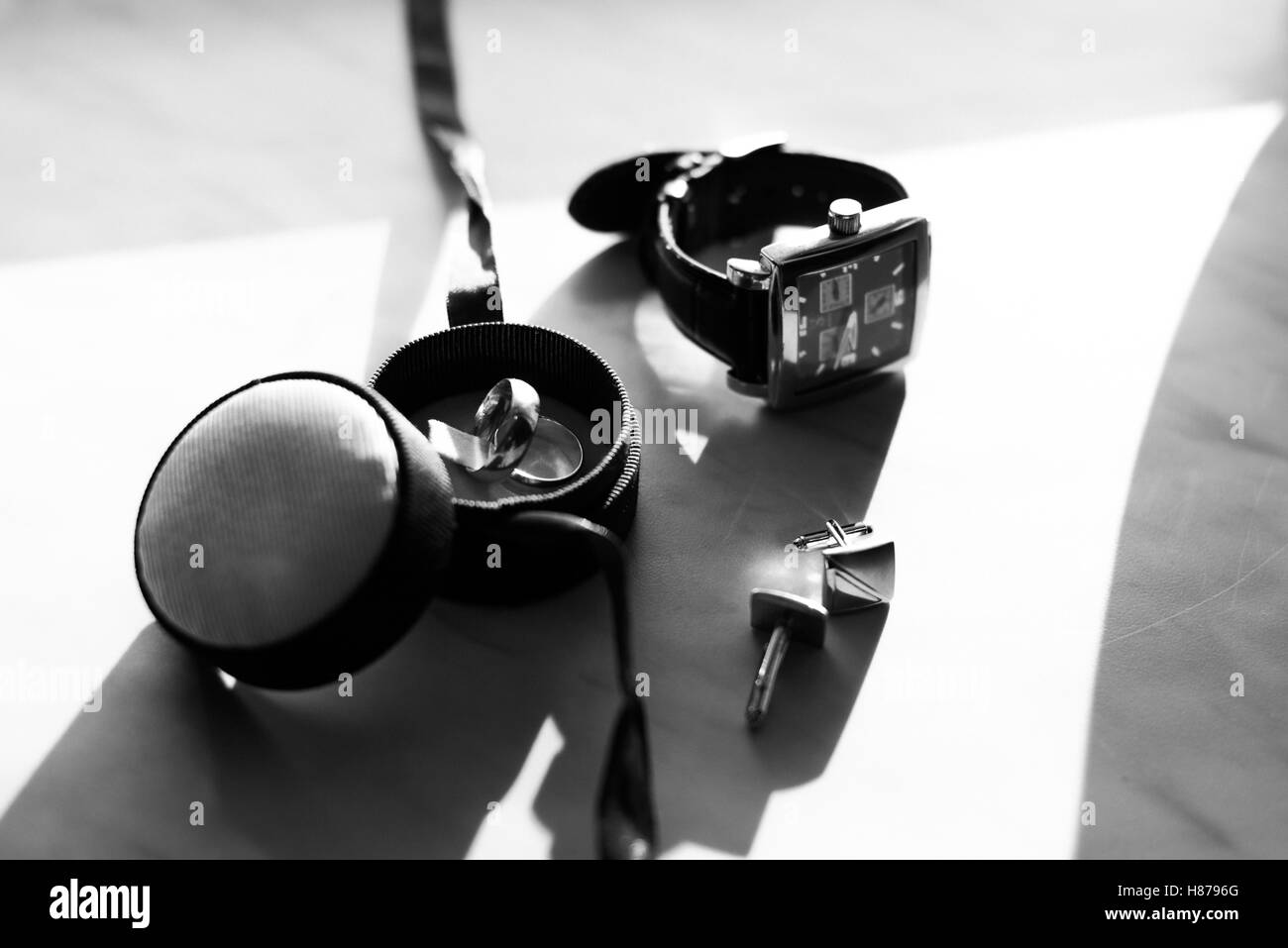 Black and white photo of watch and wedding rings lying on the ta - Stock Image