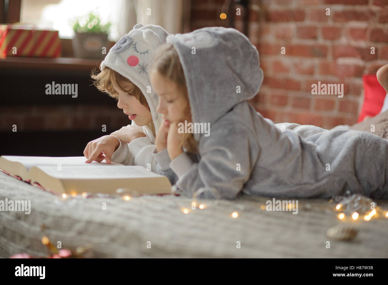 Christmas Holidays. Two children, brother and sister lie on big bed and read Christmas tales. Children dressed in - Stock Image