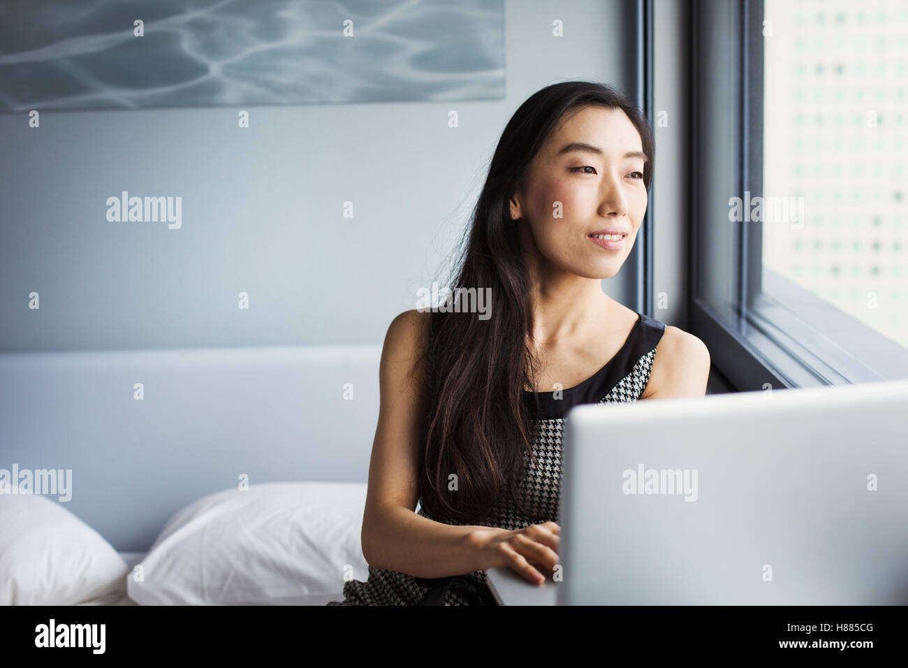 A business woman dressed, sitting on her bed using a laptop. - Stock Image