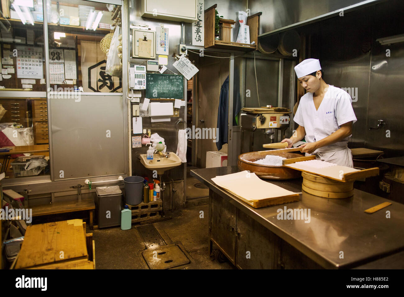 A small artisan producer of wagashi. A man mixing a large bowl of ingredients and pressing the mixed dough into - Stock Image