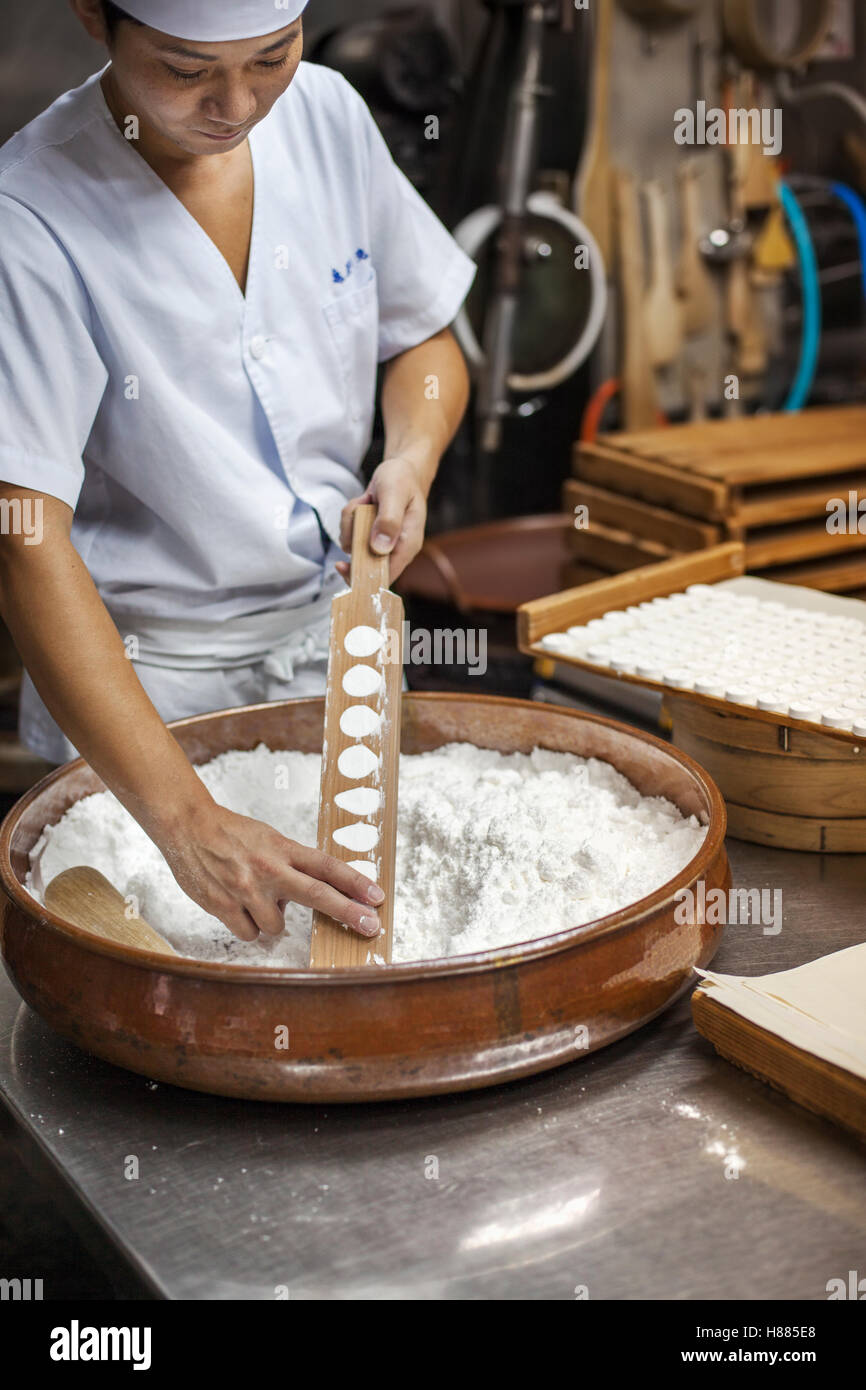 A small artisan producer of wagashi, pressing the mixed dough into moulds in a commercial kitchen. - Stock Image