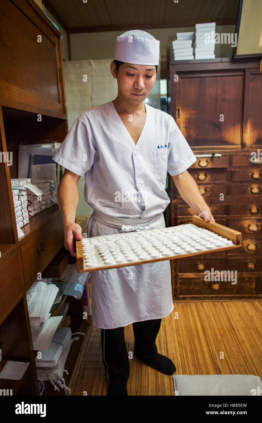 A small artisan producer of specialist treats, sweets called wagashi/ A man holding a tray of sweets. Stock Photo
