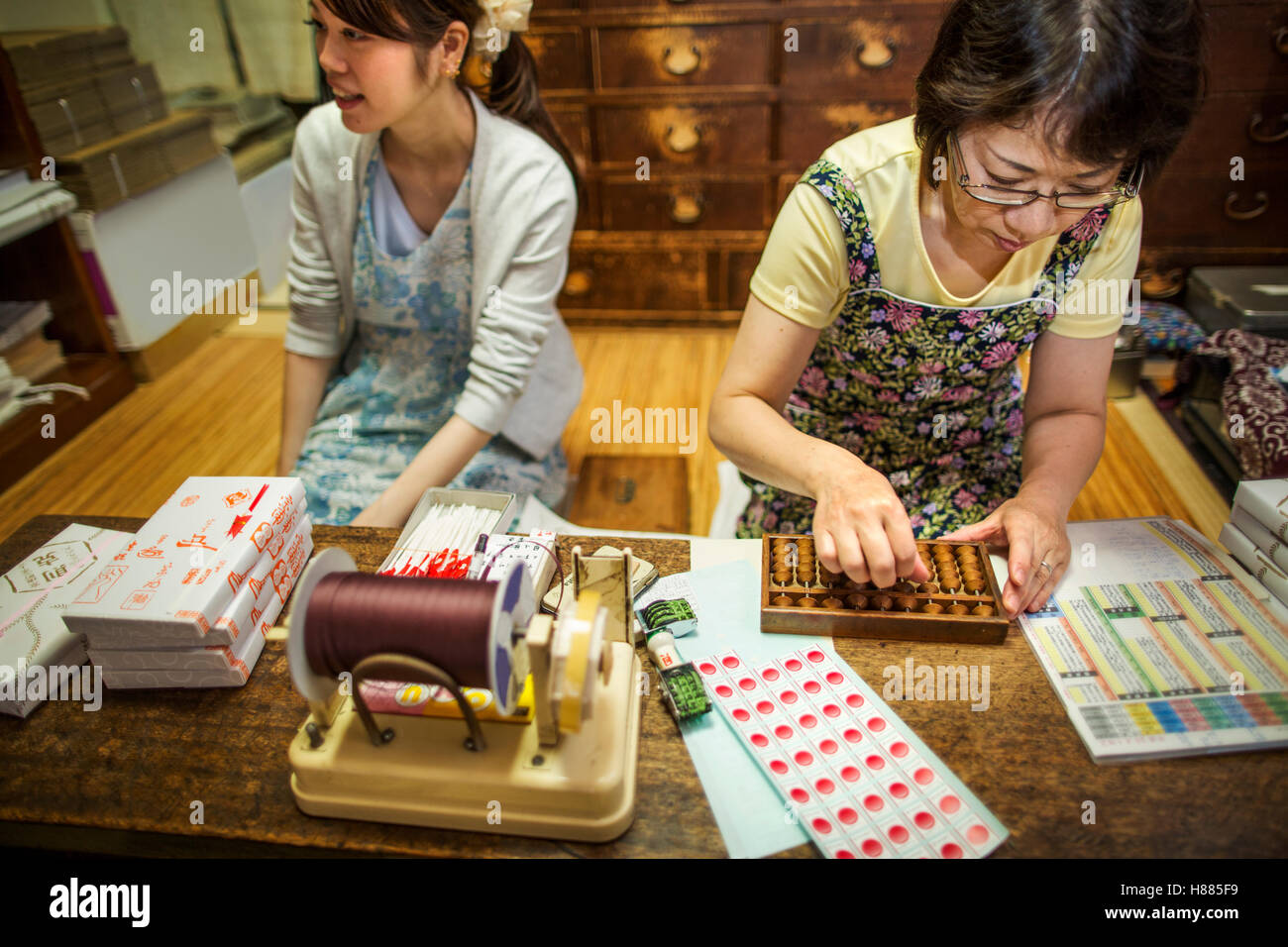 A small artisan producer of specialist treats, sweets called wagashi. Two women working packing sweet boxes for - Stock Image