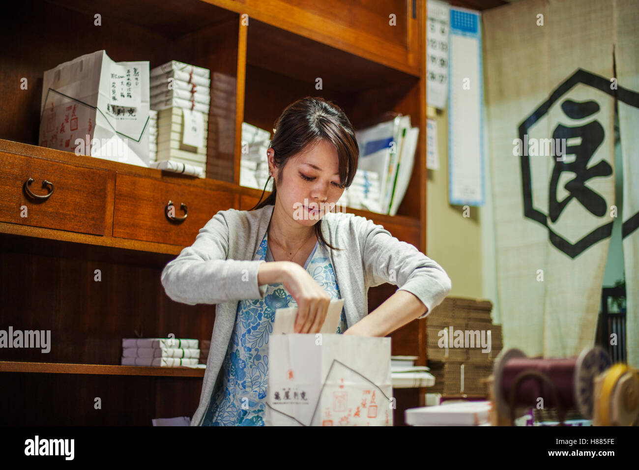 A small artisan producer of specialist treats, sweets called wagashi. A woman working packing sweet boxes for delivery. - Stock Image