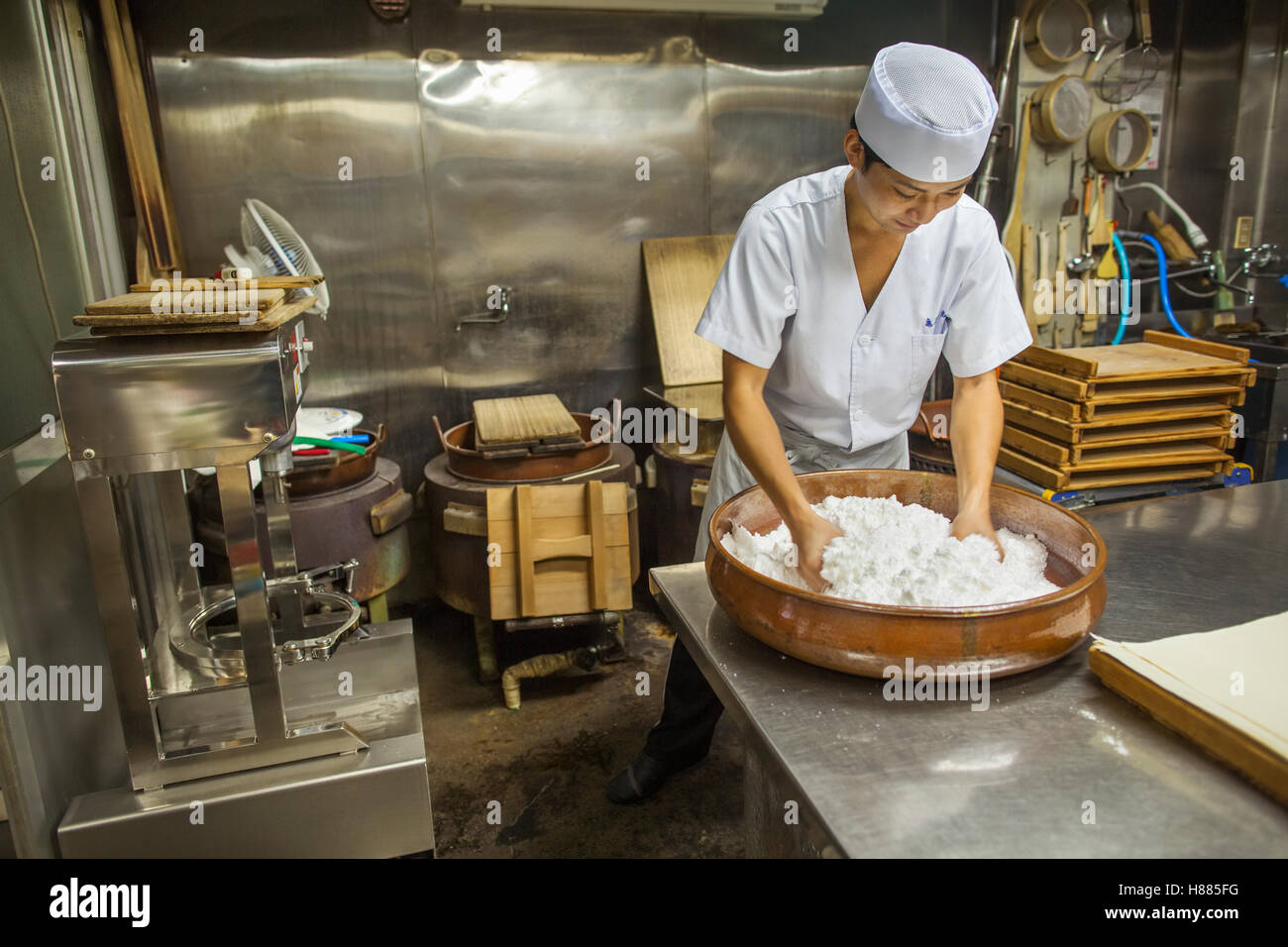 A small artisan producer of wagashi. A man mixing a large bowl of ingredients Stock Photo