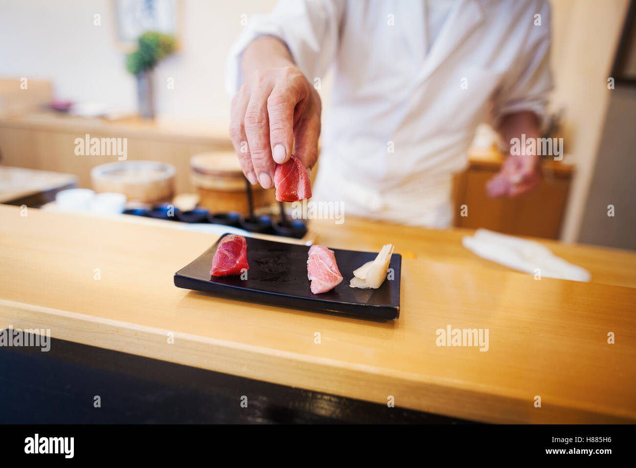 A chef working in a small commercial kitchen, an itamae or master chef presenting a fresh plate of sushi. - Stock Image