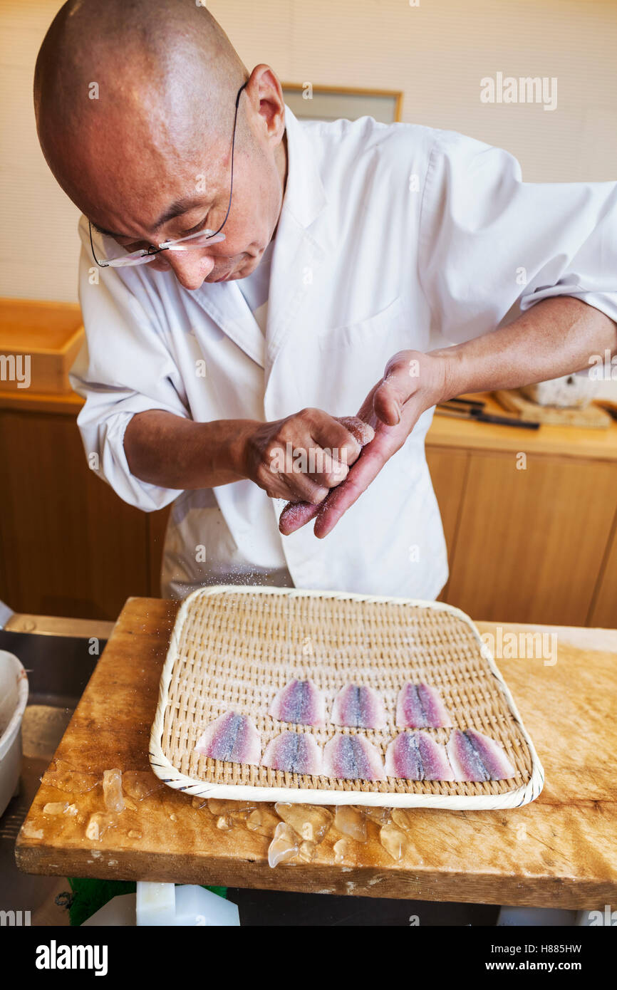 A chef working in a small commercial kitchen, an itamae or master chef making sushi, preparing fish. - Stock Image