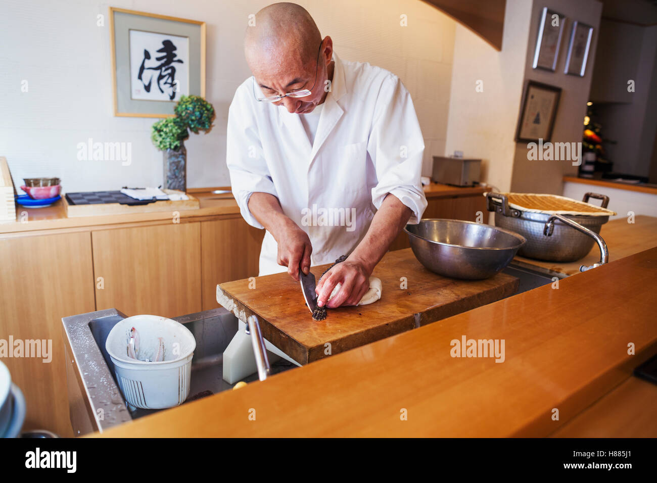A chef working in a small commercial kitchen, an itamae or master chef slicing fish with a large knife for making - Stock Image