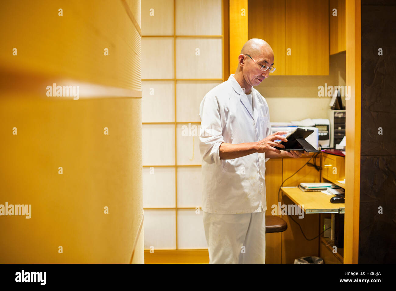 A chef in a small commercial kitchen, an itamae or master chef using a digital tablet. - Stock Image