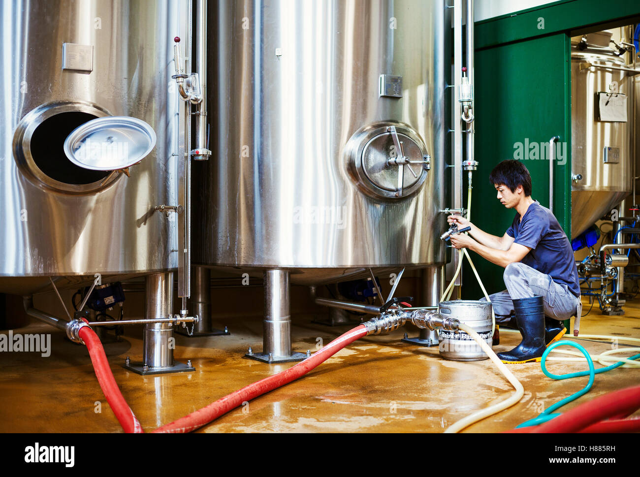 Man working in a brewery, kneeling beside a metal beer tank. - Stock Image