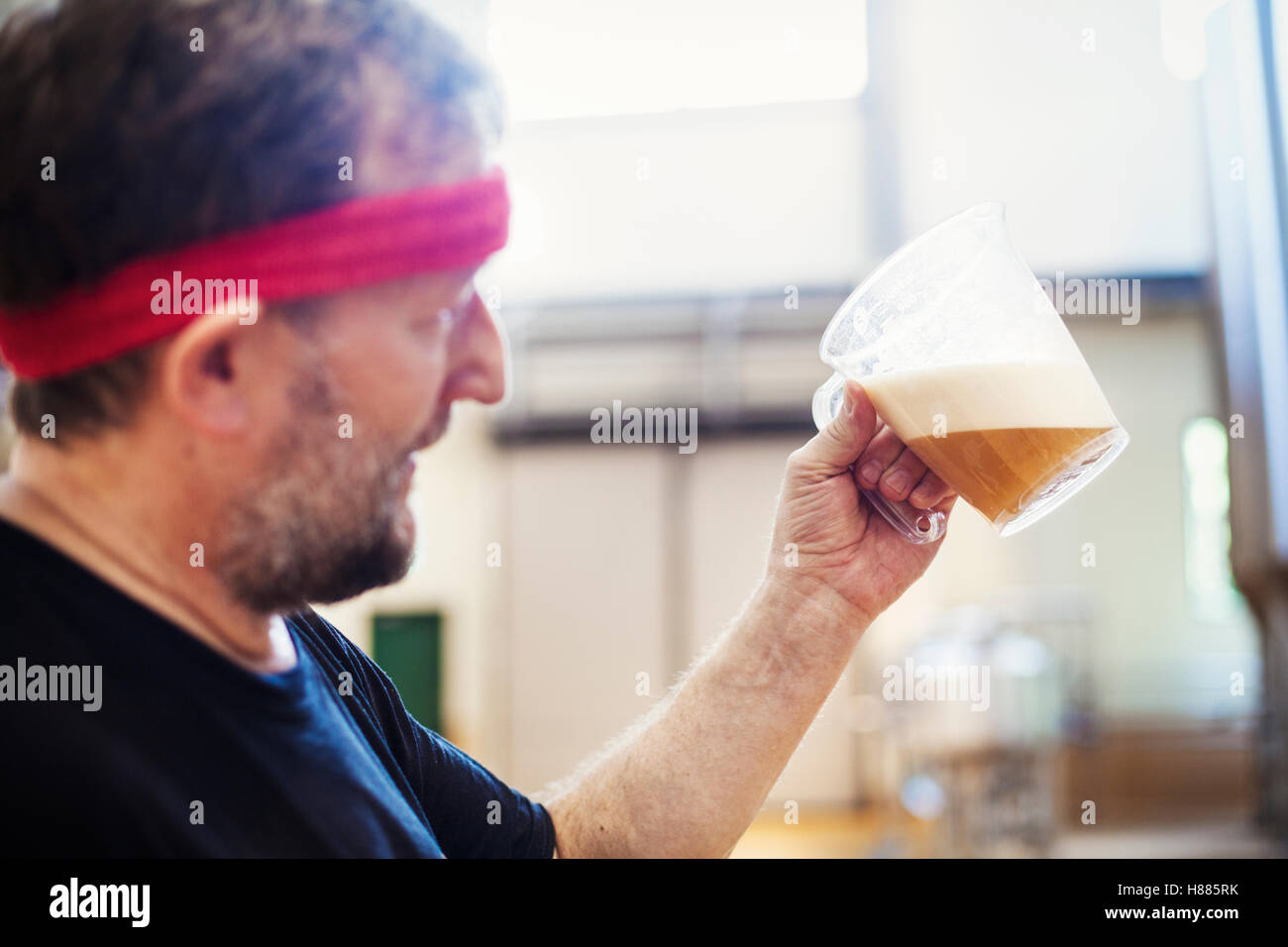 A brewer with a red bandana taking a jug of brewing beer and examining it. - Stock Image