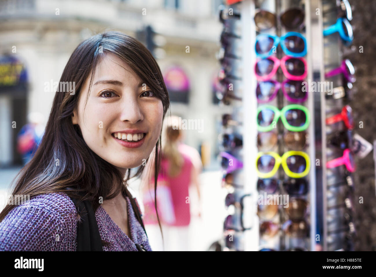 A Japanese woman trying on sunglasses in London, a summer tourist visitor. - Stock Image